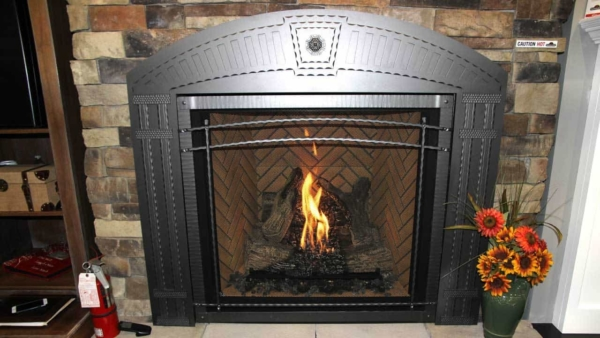 fireplace design trends might keep the traditional hearth layout but use new materials like this metal fireplace facade