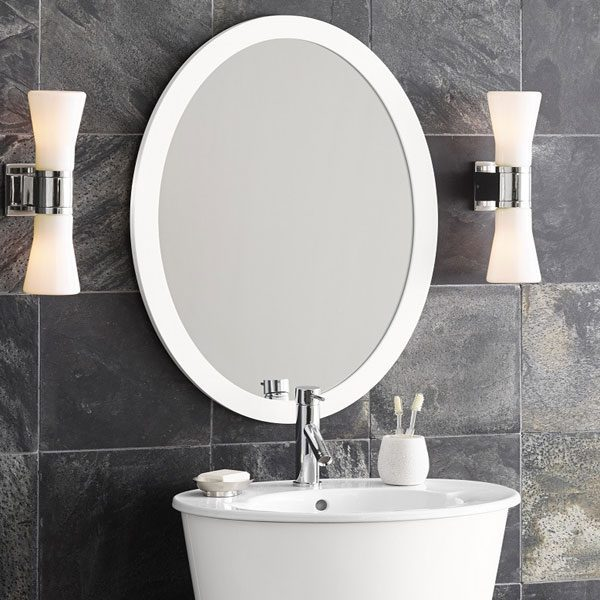 a statement mirror like this beautiful oval one with matching scones can dress up any small bathroom