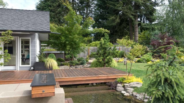 there are many landscaping ideas for your house, from shrubs to features like this bridge over a small pond