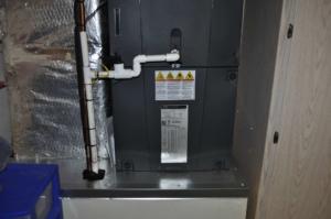 Condensate PVC line (white) outside the new Trane air handler