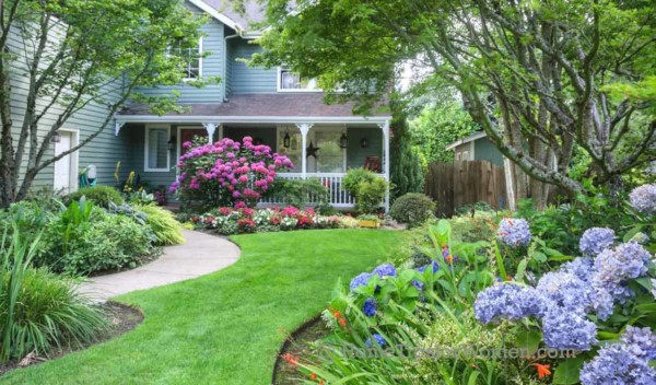 there are many ways to give your home great curb appeal from window flower boxes to a yard overflowing with flowers like this one